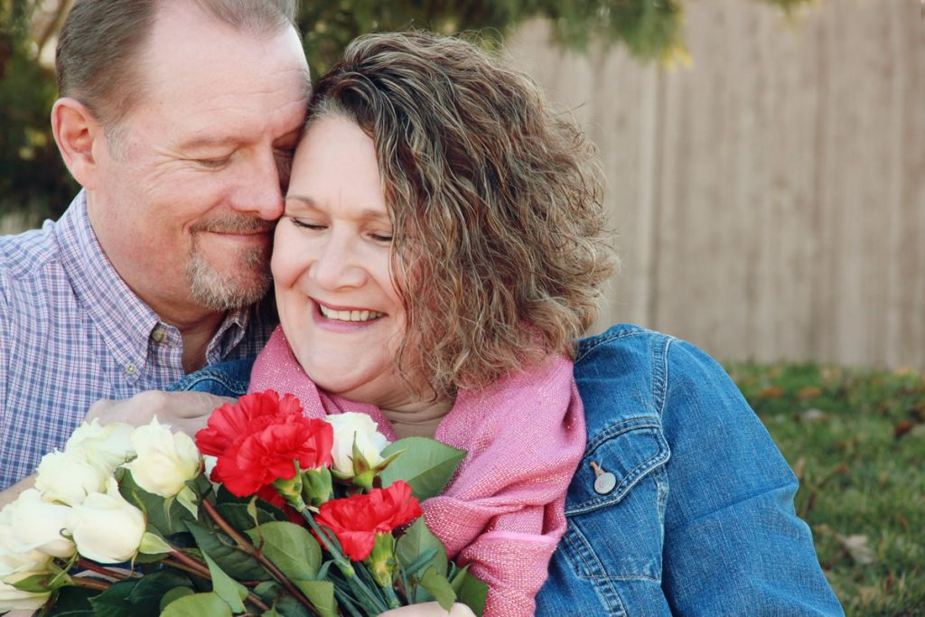 Married-Couple-Valentines-Day-Hug-with-Flower-Stock-Photo-1